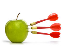TRIPLE BULLSEYE. Three red darts-arrows hit a green apple Royalty Free Stock Photography