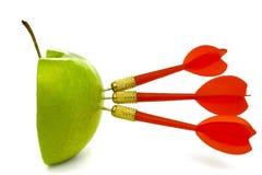 TRIPLE BULLSEYE 4. Three red darts-arrows hit a half cut green apple Stock Photo