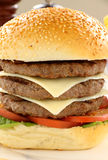 Triple Burger. Triple decker beef and cheese burger with salad ready to serve royalty free stock photos