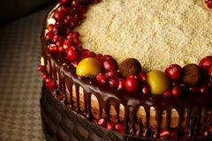 Triple chocolate cake decorated with pomegranate, cranberries and small apples. Royalty Free Stock Image