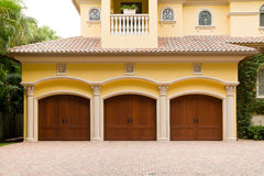 Triple Garage. Luxury house with a triple garage with wooden doors Stock Photos