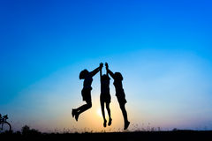 Triple is girl jumping. Silhouette of children jumping on the prairie at yellow evening horizon sea yellow sunset heaven background outdoor Stock Images