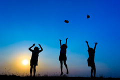 Triple is girl jumping. Silhouette of children jumping on the prairie at yellow evening horizon sea yellow sunset heaven background outdoor Royalty Free Stock Photo