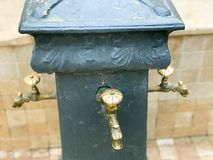 Triple gray washbasin with three carved gold taps with bronze valves for washing on the street, the beach Stock Photo