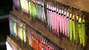 Triple hooks and colorful fishing lures in the sporting goods store. Close up stock footage