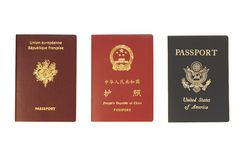 Triple identity. French, Chinese and US Passports isolated on white background Stock Images