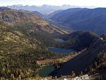 Triple Lakes in the Alpine. This image of the three lakes surrounded by mountains and golden tamaracks was taken in western MT Stock Image
