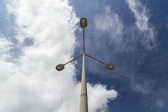 Triple lamppost against a cloudy sky Royalty Free Stock Images