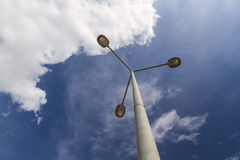 Triple lamppost against a cloudy sky Stock Photo