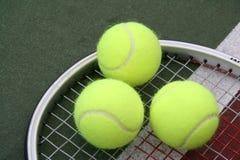 Triple Play. Triple Tennis Balls on a Racquet Stock Photo