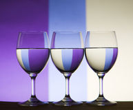 Triple refraction wine glasses. Three wine glasses filled and refracting colored background Stock Photography