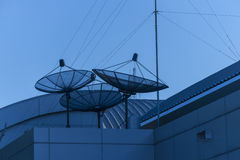 Triple satellite dishs on the building roof. Royalty Free Stock Images