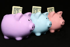 Triple Savings. Three colorful piggy banks sit in a diagional line surrounded by a black background.  The colors are purple, blue and pink.  Each has a folded Royalty Free Stock Image