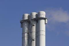 Triple tube emits smoke against the blue sky. Triple tube emits smoke against the sky Stock Image