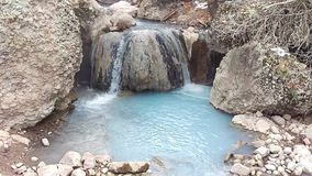 Triple Waterfall Spilling Over Boulder. A triple waterfall spilling over a boulder into a turquoise geothermal pool, fifth water hot springs trail, Utah, US stock video