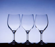 Triple white glasses on blue gradient. Three empty wine glasses with blue background royalty free stock photo