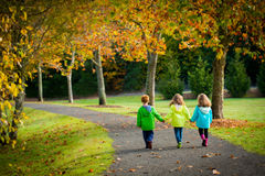 Triplet children walking on a treelined path Stock Photography