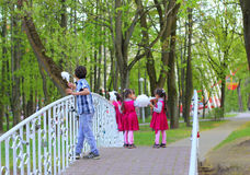 Triplet Girls with Her Older Brother. The image was taken in April 2014 in Minsk , capital of Belarus, in Gorky Park during  weekend. Three Asian girls sisters Stock Photo