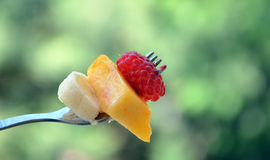 Triplet. Picture of  a Raspberry fruit,banana and peach on a fork Stock Images