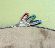 Triplet of rowboats. Three cute rowboats in mismatched colours on an artificial lake in the Loire valley Stock Images