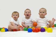 Triplets de bébé riant et jouant avec les boules colorées Images stock