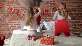 Triplets sisters in pajamas have arranged fight by pillows. The bedroom is decorated by christmas garlands and xmas stock footage