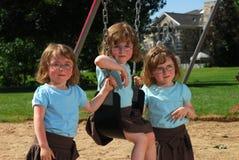 Triplets sur le swingset Photographie stock libre de droits