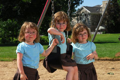 Triplets on the swingset Royalty Free Stock Photography