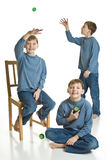 Triplets Yo-yoing. Three matching boys in blue playing with yo-yos. Isolated on a white background Royalty Free Stock Photo