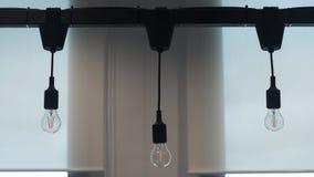 Triplicar-se do pendurado abaixo da luz fora da lâmpada no feixe no escritório Foto de Stock Royalty Free