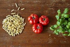 Triplicar-se fora dos tomates e da manjericão da massa fotografia de stock royalty free