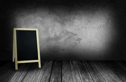 Tripod blackboard in interior room with gray stone wall Stock Images