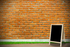 Tripod blackboard in interior room with molder brick wall blackg Royalty Free Stock Photo