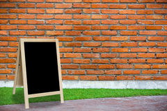 Tripod blackboard in interior room with molder brick wall Stock Photo
