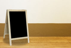 Tripod blackboard in interior room with  wall blackground Royalty Free Stock Photos
