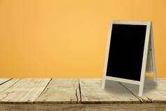 Tripod blackboard w wewnętrznym pokoju z pomarańcze ściany tłem Obrazy Stock