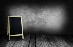Tripod blackboard w wewnętrznym pokoju z szarą kamienną ścianą Obrazy Stock