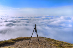 Tripod on a mountain top. Tripod for photo camera set up on a mountain top surrounded by clouds Royalty Free Stock Image