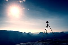 Tripod with red baseball cap on the peak ready for photography. Sharp autumn rocky peaks increased from heavy fog. Stock Photo