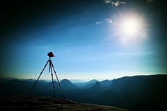 Tripod with red baseball cap on the peak ready for photography. Sharp autumn rocky peaks increased from heavy fog. Royalty Free Stock Image