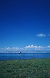 A tripod  under the blue sky. A tripod on the green meadow under the blue sky Stock Photography