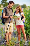 Trippers. Portrait of young hikers looking at map in the countryside at summer Royalty Free Stock Photo