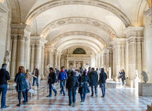 Trippers in the visit of Louvre Museum. PARIS - APRIL 07: Tourists walk in Museum Louvre on April 07, 2013 in Paris, France Royalty Free Stock Photography