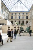 Trippers in the visit of Louvre Museum. PARIS - APRIL 07: Tourists walk in Museum Louvre on April 07, 2013 in Paris, France Royalty Free Stock Photo