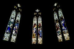 Triptych of stained-glass windows from St Patrick`s Cathedral on black background in Melbourne Australia royalty free stock photo