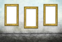 Triptych. Three vertical golden frames on dirty wall Stock Photo