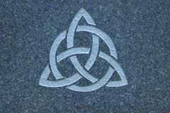 Triquetra / Trinity knot on stone surface. Close up on Triquetra / Trinity knot on stone surface. parallel doubled-lines are in the graph, the design is used as Stock Image