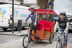 Trishaw and cyclist riding on the road Stock Photo