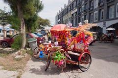 Trishaw dekorerade med färgrika blommor på gatan i Malacca arkivbilder