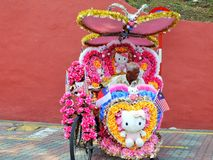 Trishaw dekorerade med färgrika blommor som väntar på kunden i Malacca, Malaysia Arkivbilder
